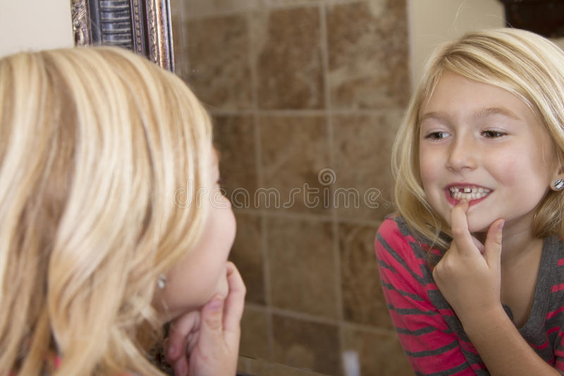 Child looking in mirror at missing front tooth. Child looking in mirror and pointing at missing front tooth stock photo