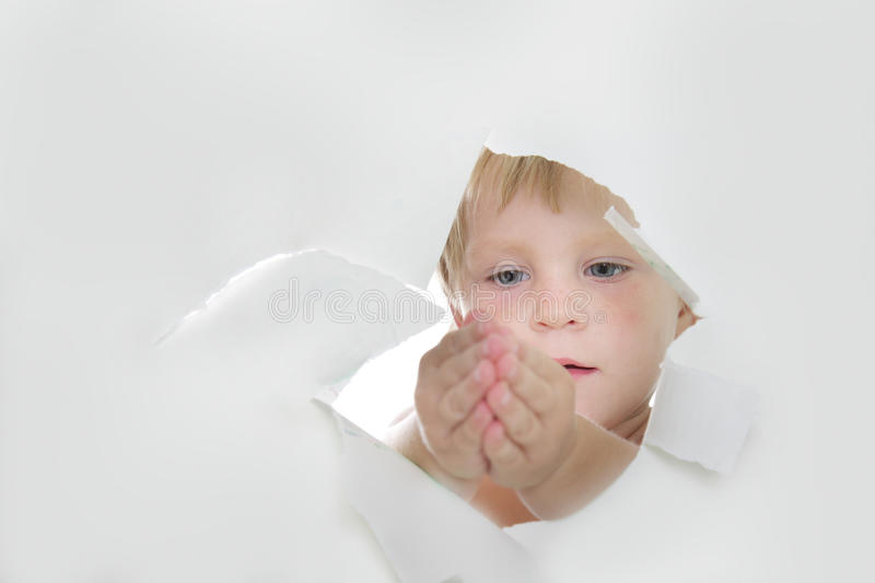 Child looking out from hole in paper stock image