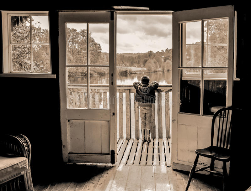 Child looking over the water. A picture of a young child looking out across a pond from within a boathouse stock photos
