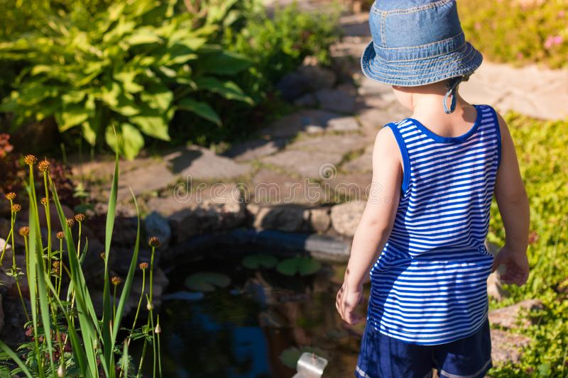 The child is looking at the pond stock images