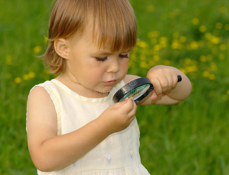 Child looking at snail through magnifying glass royalty free stock image