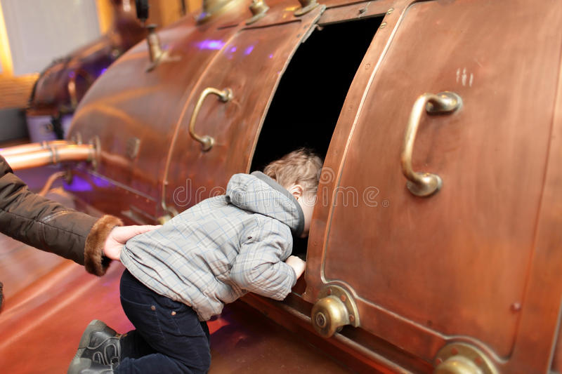 Child looking at tank. In the brewery royalty free stock photo