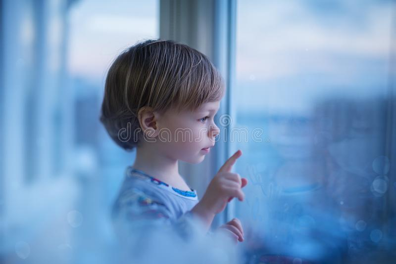 Child looking at window stock photo
