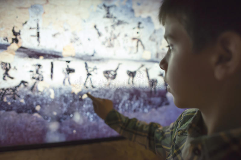 Child looks at aancient mural royalty free stock images
