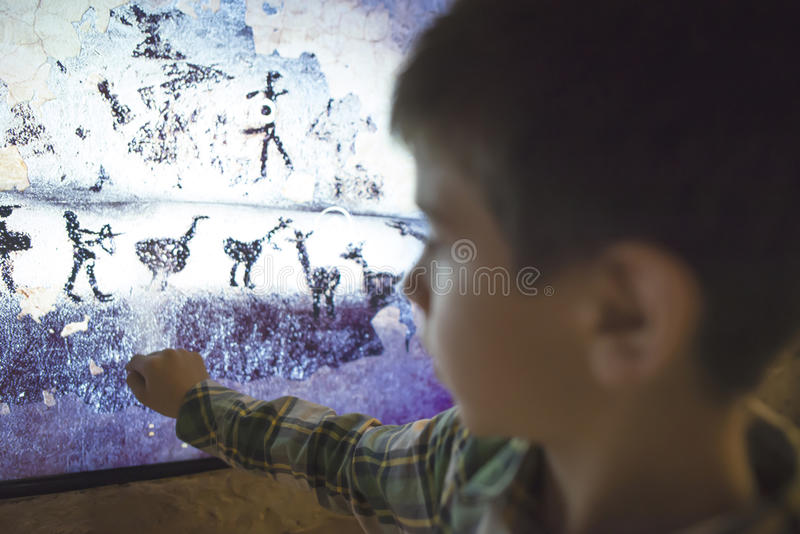 Child looks at aancient mural stock photos