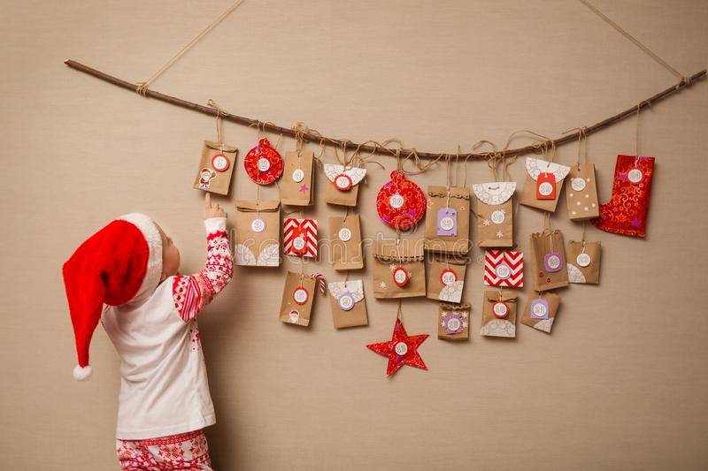 Child looks at the advent calendar. Baby girl in a Christmas hat and pajamas shows on first gift.  stock images