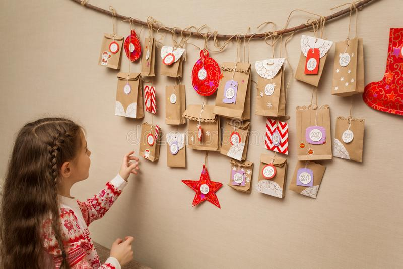 Child looks at the advent calendar. option DIY to wait for Christmas for kids.  stock images