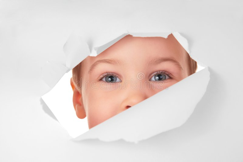 Child Looks In Hole In Sheet Of Paper Royalty Free Stock Photos