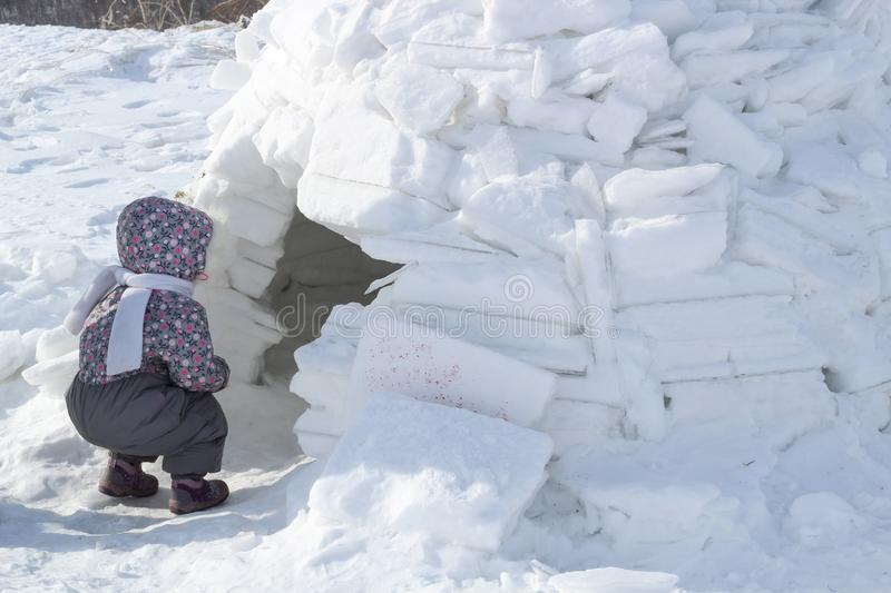 The child looks into the house of Eskimos-igloo. The child looks into the house of Eskimos-igloo stock photo