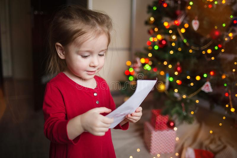 A child looks at a letter to Santa Claus at home on the background of a Christmas tree. girl holding a piece of paper stock photos