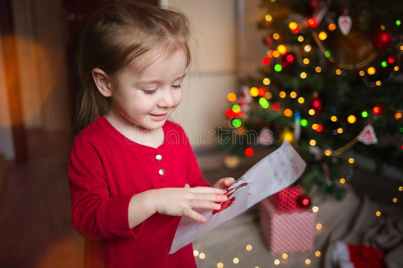 A child looks at a letter to Santa Claus at home on the background of a Christmas tree stock photos