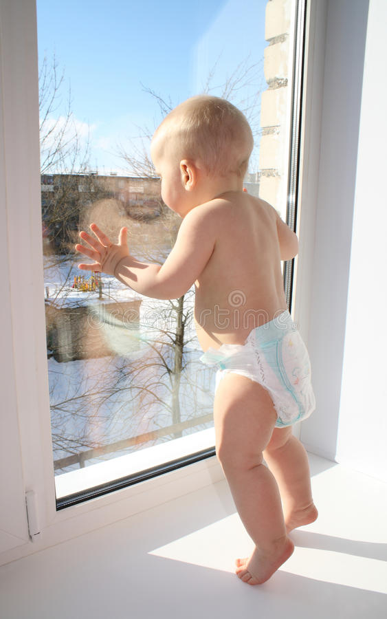 The child looks out of the window stock photography