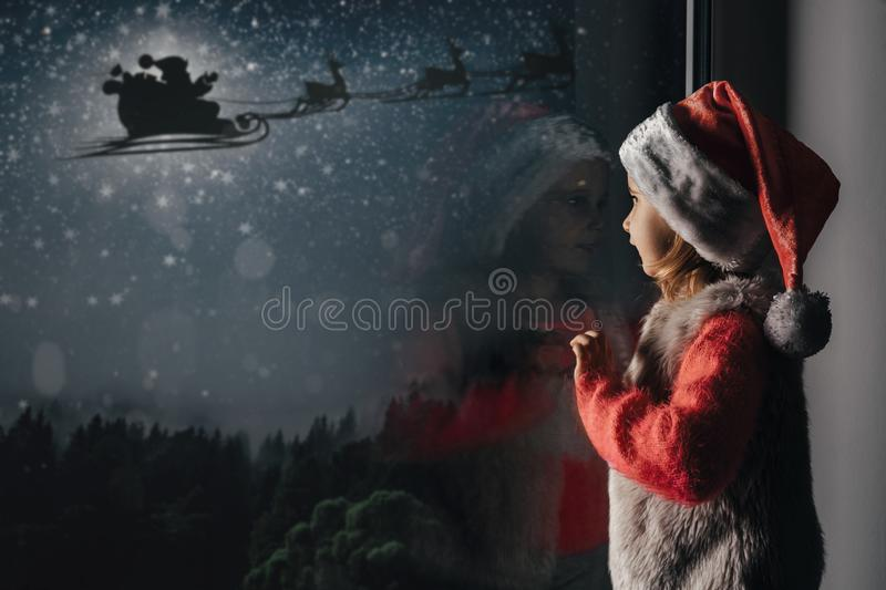 child looks out the window on Christmas day royalty free stock photography
