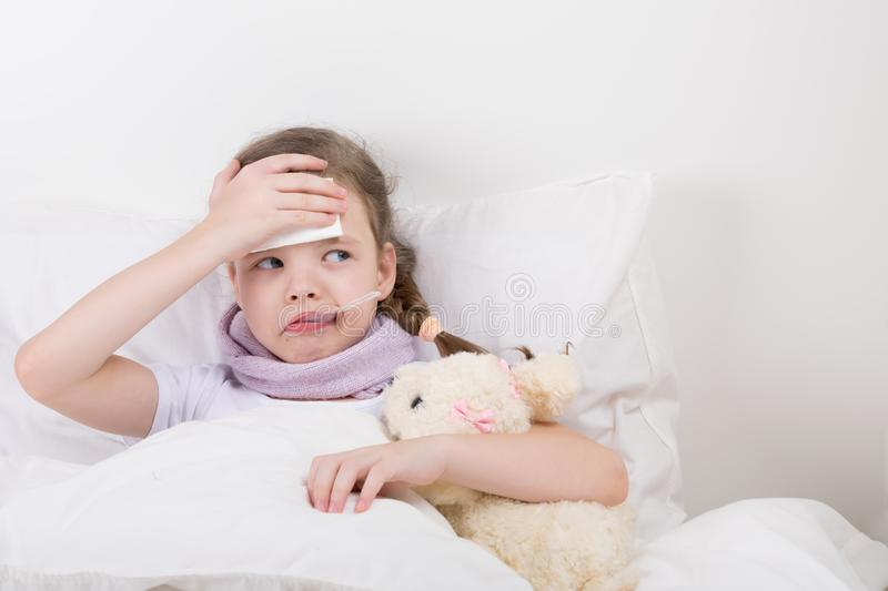 child lying in bed with a bear holding onto his forehead, from a headache, looking to the right royalty free stock photography