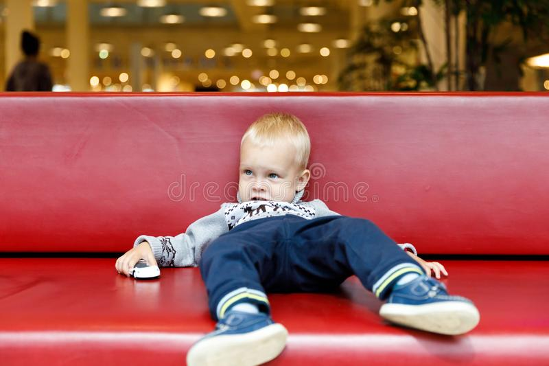 Child is lying on the couch in the shopping center or mall. Little boy tired during shopping with parents.  stock images