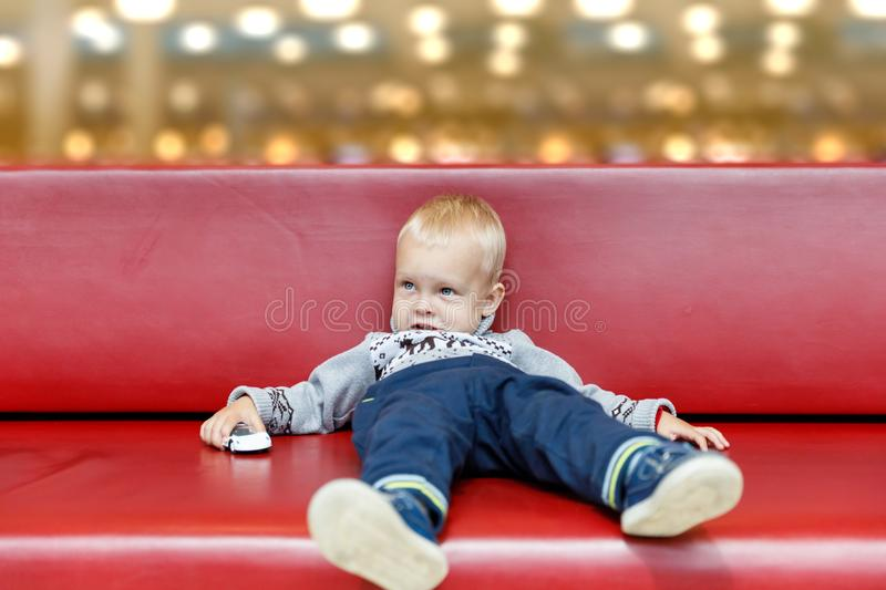 Child is lying on the couch in the shopping center or mall. Little boy tired during shopping with parents stock images
