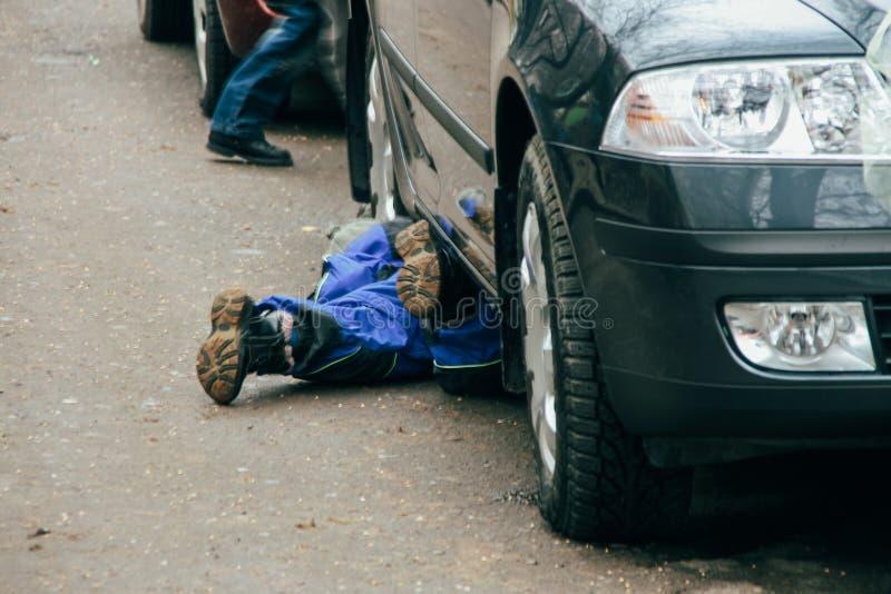 Сршдв lying under the car royalty free stock image