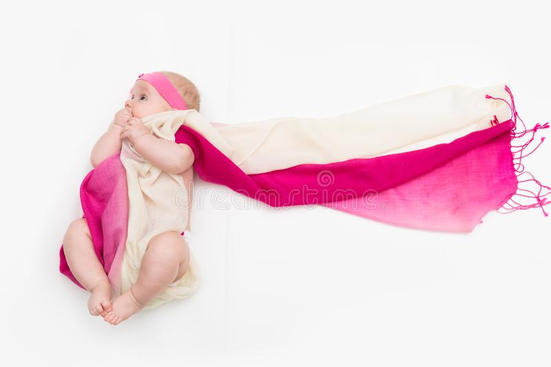 Child lying on white background wrapped in long fabric stock photo