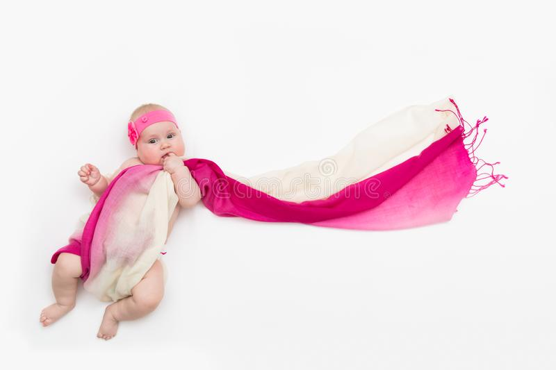Child lying on white background wrapped in long fabric stock images