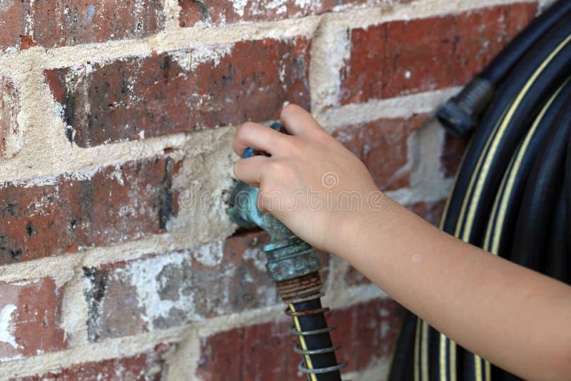 Child& x27; a mão de s gerencie o torneira de água da mangueira foto de stock