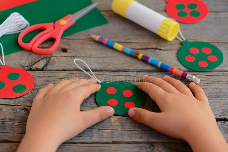 Child made bright Christmas balls from cardboard paper. Child shows Christmas ball. Step. Scissors, pencil, glue stick stock image