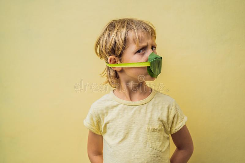 The child made himself a face mask from the leaves to protect himself from air pollution. Air purification for children stock photos