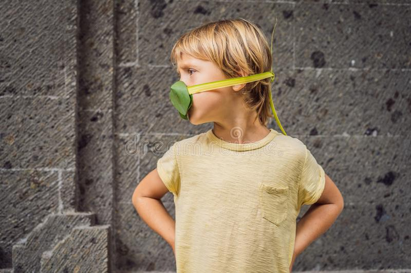 The child made himself a face mask from the leaves to protect himself from air pollution. Air purification for children royalty free stock image