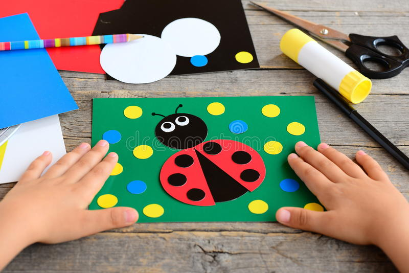 Child made a ladybird from colored paper. Summer card with paper ladybug, stationery on a wooden table. Simple paper circle crafts. Developing motor skills stock photos