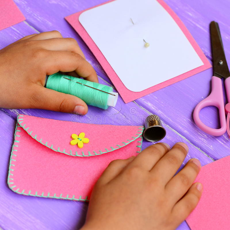 Child made a simple felt purse. Handicraft supplies on a wooden table. Fun and easy teaching kids to hand sew. Kids sewing concept. Purse sewing pattern. Purse stock photography