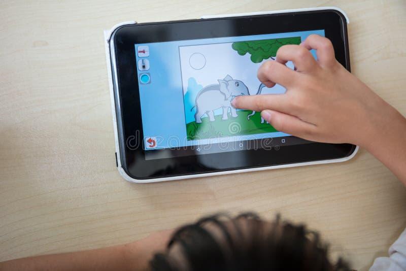 Child& x27 ; mains de s jouant la tablette images libres de droits