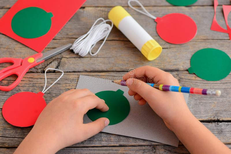 Child makes Christmas balls out of cardboard. Child draws a ball on a cardboard with a template and a pencil. Step. Stationery royalty free stock images