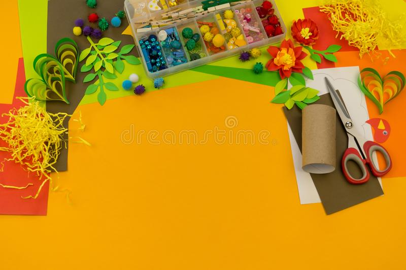 Child makes craft tree of paper. Orange background and materials for creative classes stock photography