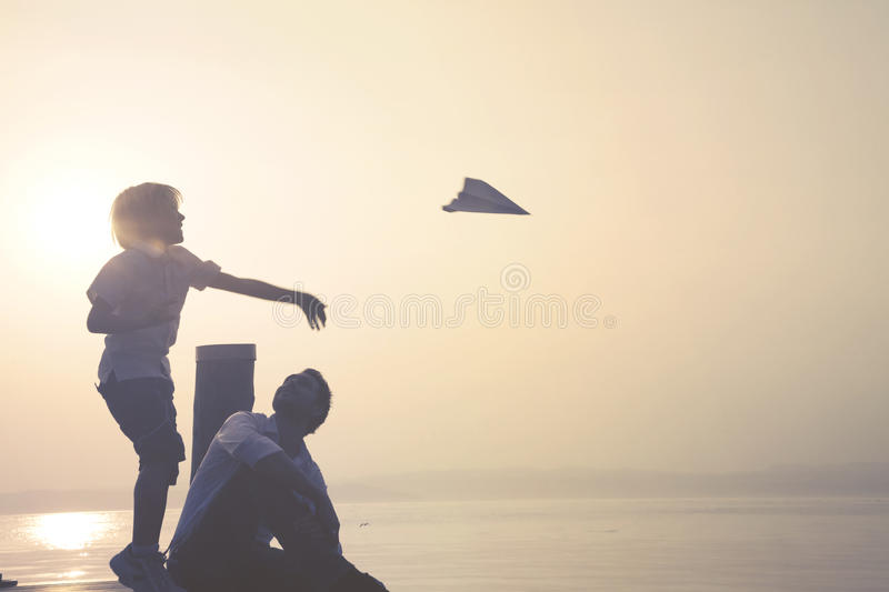 Child makes fly his paper airplane. Happy child makes fly his paper airplane stock images