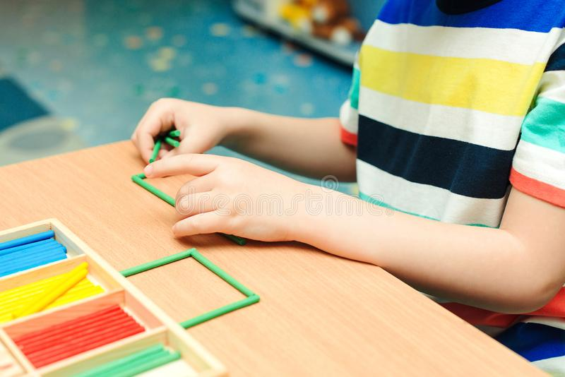 Child makes geometric forms from colorful sticks. Preschool education and development. Primary class of school. Kid at math class royalty free stock images