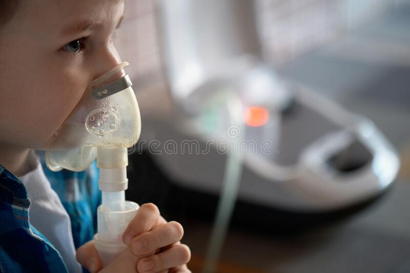 Child makes inhalation at home with nebulizer on out of focus background. Example of combating respiratory diseases such as stock photography