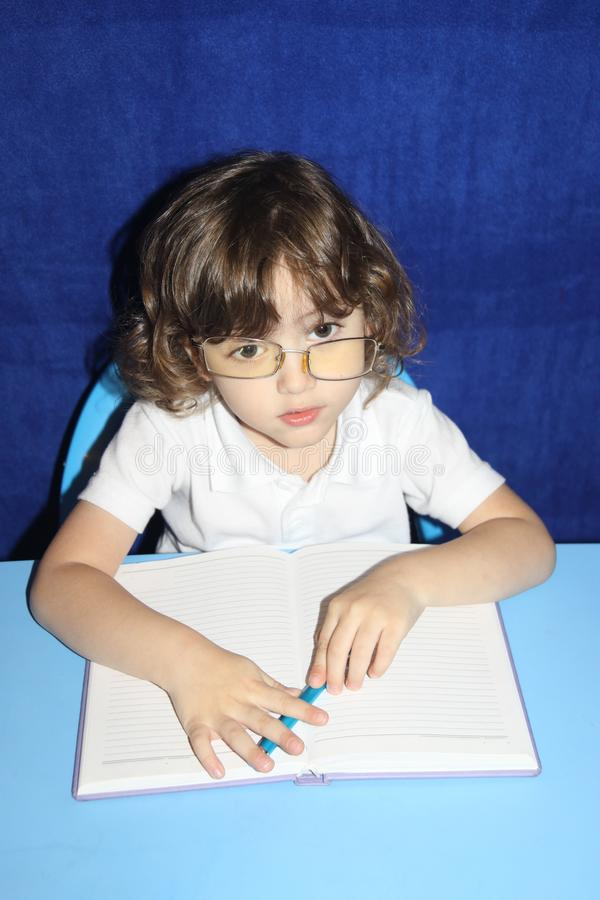 The child makes lessons with a serious look in glasses stock photos