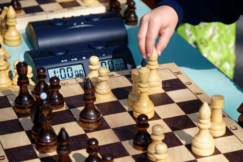 The child makes a move in a chess game. The game of intelligence royalty free stock image
