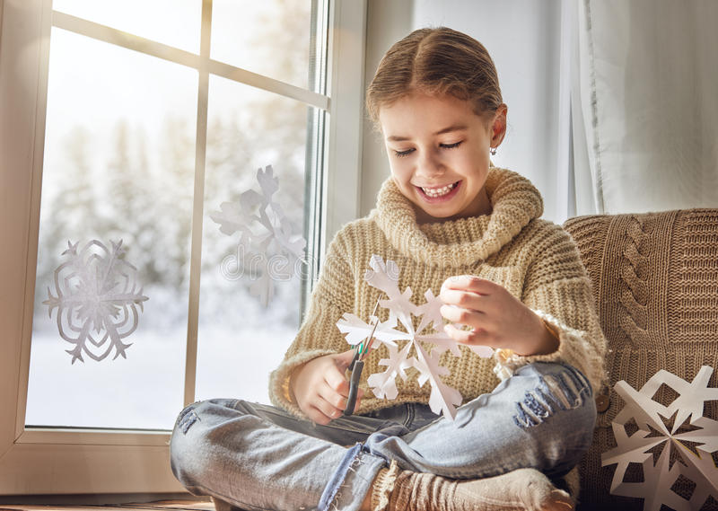 Child makes paper snowflakes stock photography