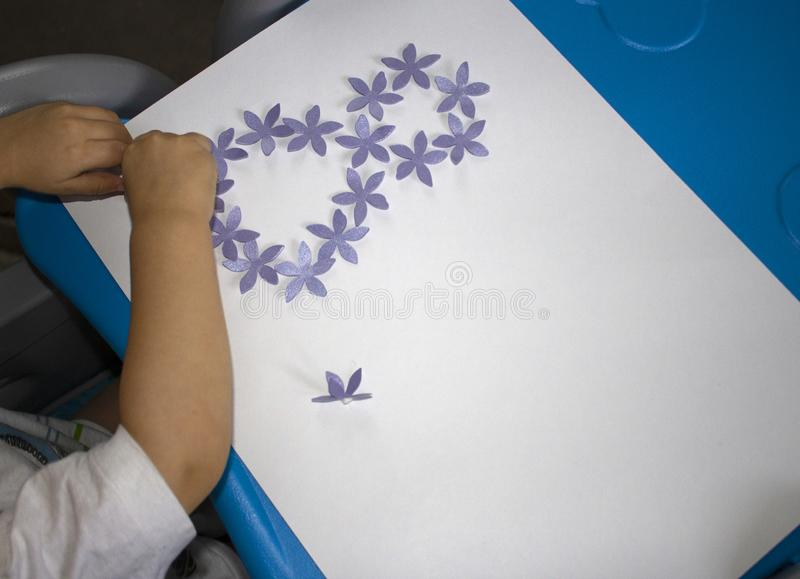 Child making postcard with picture 8 march. Kid paperwork. Material for creativity. Kindergarten stock photography