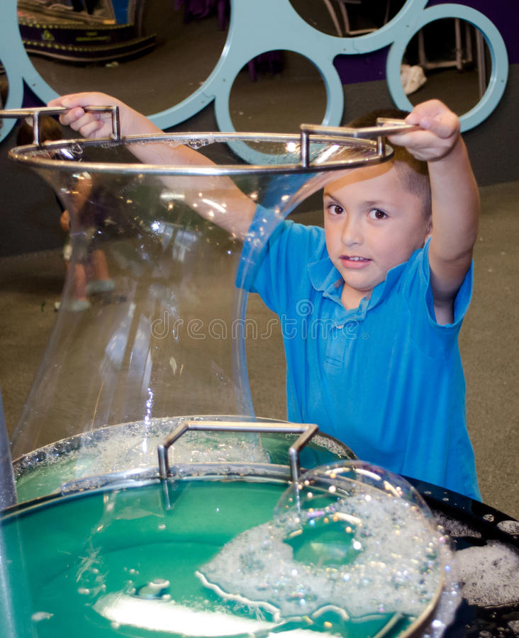 Child making bubbles at the denver children's' museum. A little hispanic boy learns about bubbles and science at the Denver Children's museum in Denver Colorado royalty free stock photo