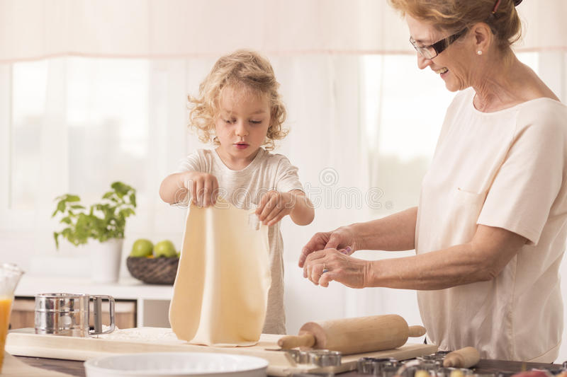 Child making cake with grandmother royalty free stock photo