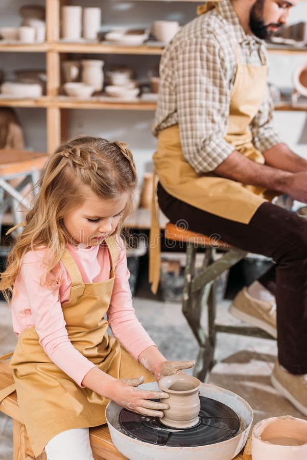 child making ceramic pot on pottery wheel with teacher stock image
