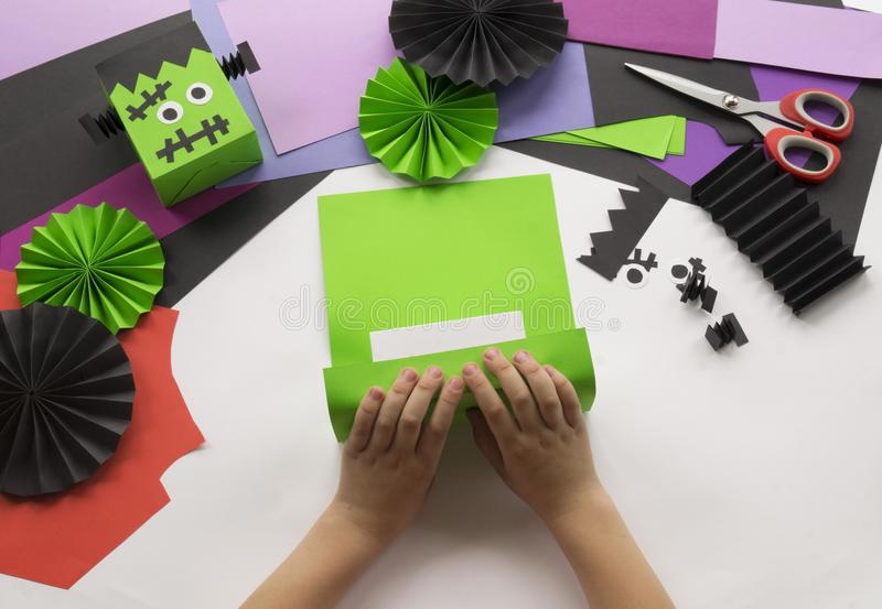 A child making decorum of Halloween from colored paper. royalty free stock image