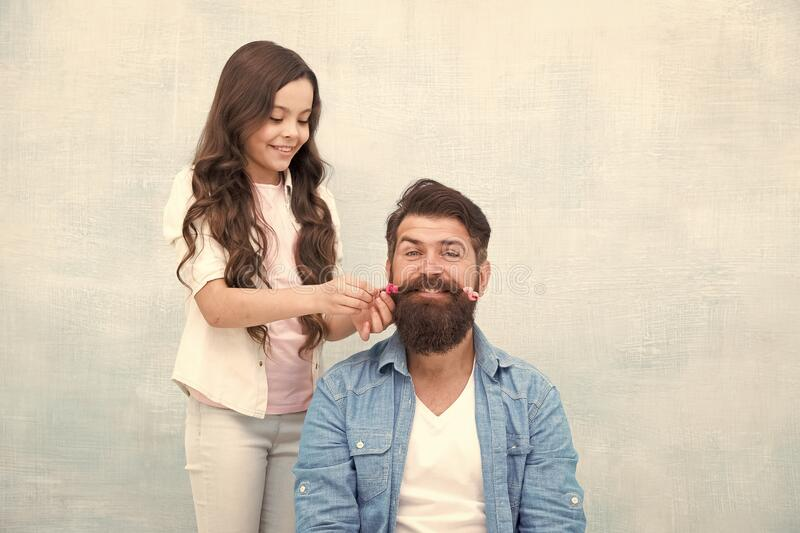 Child making hairstyle styling father beard. Being parent means present for kid interests. Change hairstyle. Create royalty free stock photo