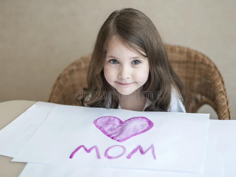 Child making homemade greeting card. A little girl paints a heart on a homemade greeting card as a gift for Mother Day royalty free stock photos