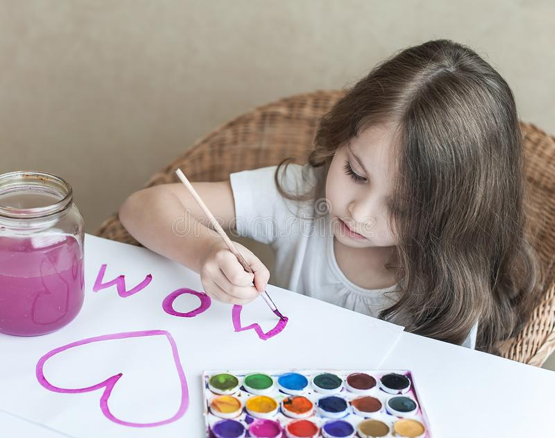 Child making homemade greeting card. A little girl paints a heart on a homemade greeting card as a gift for Mother Day. Traditional play concept. Arts and stock photo