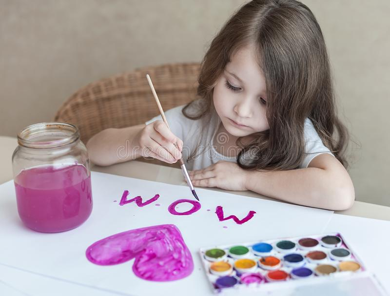 Child making homemade greeting card. A little girl paints a heart on a homemade greeting card as a gift for Mother Day. Traditional play concept. Arts and royalty free stock images