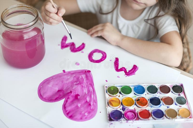 Child making homemade greeting card. A little girl paints a heart on a homemade greeting card as a gift for Mother Day. Traditional play concept. Arts and stock photography