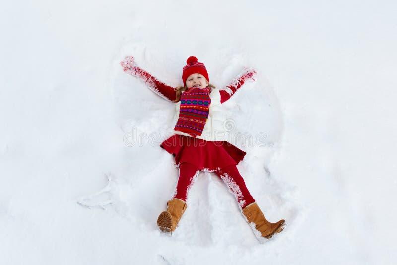 Child making snow angel. Kids winter outdoor fun stock photos
