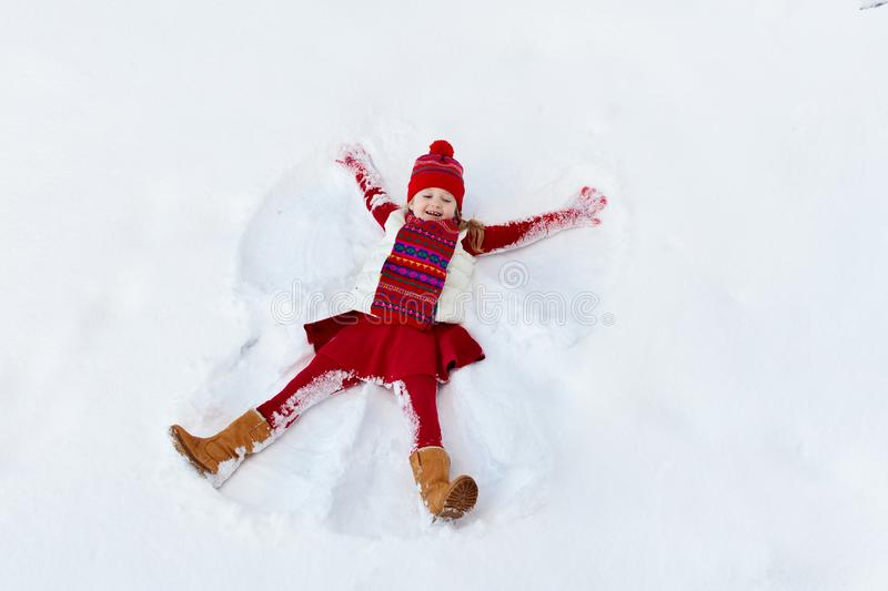 Child making snow angel on sunny winter morning. Kids winter outdoor fun. Family Christmas vacation. Little girl playing in snow stock images